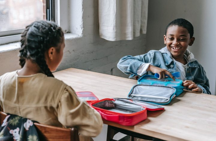 cheerful black schoolboy with lunch box against unrecognizable girl
